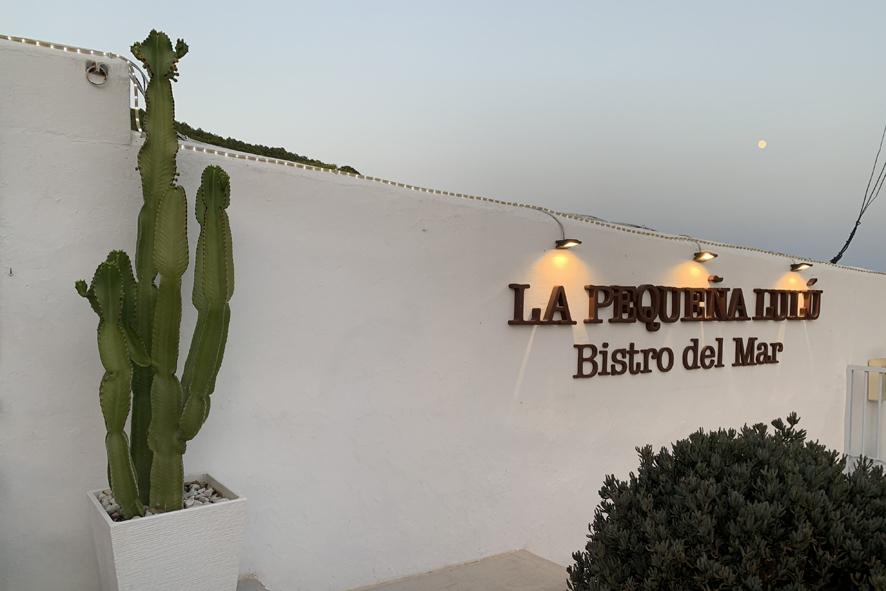 Entrada del coqueto Restaurante La Pequeña Lulú y luna llena sobre el abalconado